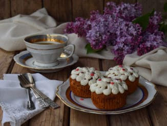 Romantic composition of  bouquet white and purple lilacs, cupcakes with curd cream, cups coffee on wooden background.